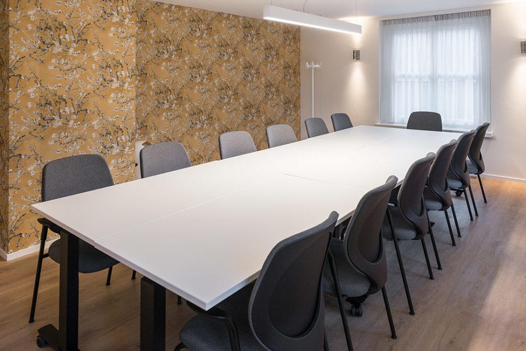 vergaderruimte behang zwart stoelen wit tafel